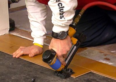 Using tool to install hardwood floor pieces.